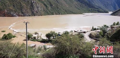 西藏昌都市官方通報,10月11日凌晨4時許,西藏昌都市江達縣波羅鄉境內的金沙江兩岸發生山體滑坡,滑坡體量大,主河道被堵,導致水位上漲迅猛,形成堰塞湖,部分橋梁和農田被淹,目前無人員傷亡的報告。圖為金沙江水位上漲迅猛,淹沒瞭當地民房。中新社記者 昌都市宣傳部供圖