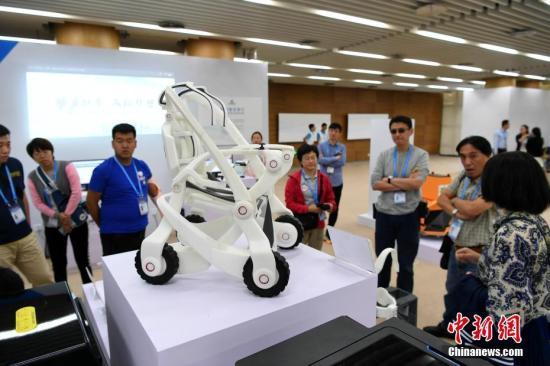 """10月13日,第四届中国""""互联网+""""大学生创新创业大赛总决赛在厦门大学举行。无人机、自助售饭机、人偶互动、全息3D智能视频、机器人轮椅、3D打印假肢手臂等大学生研发设计的产品亮相会场,以""""90后""""为主的创新创业生力军已全面发力,释放出""""青年+创新创业""""的无穷力量。图为3D打印个性化定制机器人轮椅展示。中新社记者 王东明 摄"""