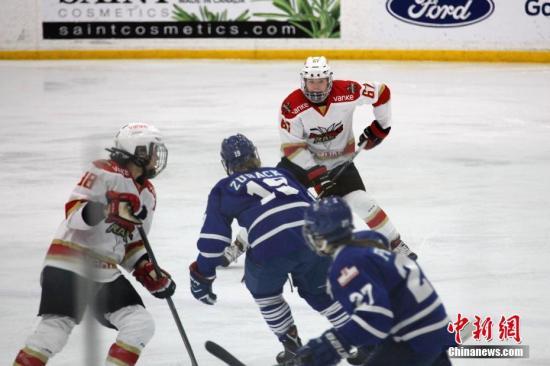 当地时间10月13日晚,在加拿大女子冰球联赛(CWHL)2018至2019赛季揭幕战中,来自中国的深圳昆仑鸿星万科阳光队在多伦多客场作战,以5比1力克对手多伦多怒火队,迎来开门红。图为深圳昆仑鸿星万科阳光队队员(红白球衣)组织进攻。CWHL是世界女子冰球最高水平联赛。这也是来自中国的冰球俱乐部第二年参加这一联赛。 中新社记者 余瑞冬 摄