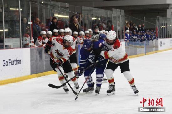 当地时间10月13日晚,在加拿大女子冰球联赛(CWHL)2018至2019赛季揭幕战中,来自中国的深圳昆仑鸿星万科阳光队在多伦多客场作战,以5比1力克对手多伦多怒火队,迎来开门红。图为深圳昆仑鸿星万科阳光队队员(红白球衣)夹击对手。CWHL是世界女子冰球最高水平联赛。这也是来自中国的冰球俱乐部第二年参加这一联赛。 中新社记者 余瑞冬 摄