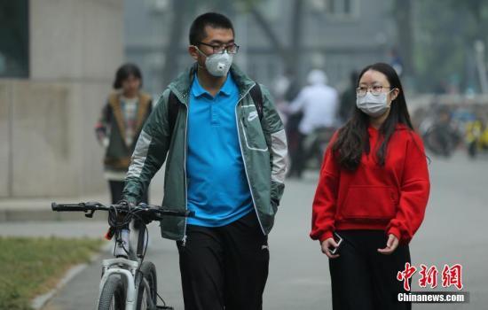10月15日8时,北京民众戴口罩防护出行。当日,北京城六区PM2.5平均浓度为173微克/立方米,属于五级重度污染水平。市环保局监测中心表示,当日白天北京受弱气压场作用,扩散条件较不利,预计空气质量仍维持为中度至重度污染水平,预计将到达此次污染过程的峰值。中新社记者 杨可佳 摄