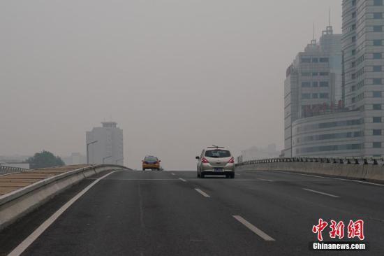 资料图:10月15日,北京海淀区航天桥被雾霾笼罩。中新社记者 崔楠 摄