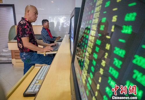 10月15日,海口某证券公司营业部的股民关注股市动态。截至收盘:沪指报2568.10点,跌1.49%;深指报7444.48,跌1.51%;创业板指数报1250.22点,跌1.43%。中新社记者 骆云飞 摄