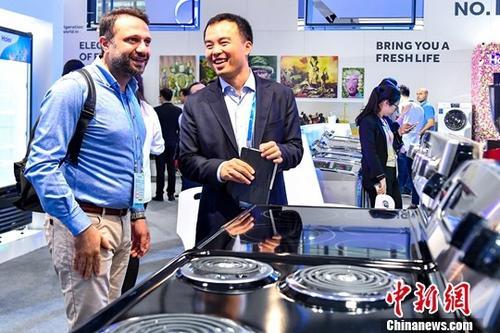 10月15日,家用电器参展商为采购商介绍产品性能。当日,第124届中国进出口商品交易会(广交会)在广州开幕,吸引来自210多个国家和地区的近20万名采购商到会。中新社记者 陈骥旻 摄