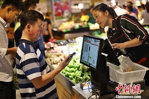 资料图为南京民众在当地一家菜场内购买蔬菜。 记者 泱波 摄