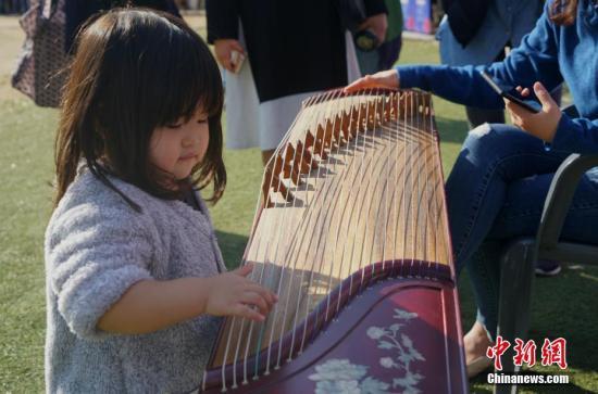 """10月21日,2018第六届""""首尔・中国日""""在首尔举行,一系列中国传统文化体验活动纷纷亮相。图为当地儿童体验中国传统乐器。<a target='_blank' href='http://www-chinanews-com.changxiangair.com/'>中新社</a>记者 曾鼐 摄"""