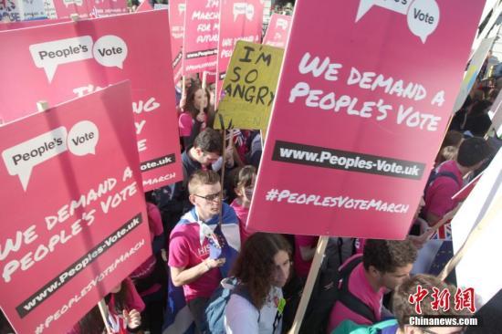 """资料图:当地时间10月20日,67万英国民众汇集在伦敦议会广场举行示威游行活动,呼吁对英国脱欧最终协议举行全民投票。图为示威游行人群高举标语牌,呼吁举行""""人民投票""""。 <a target='_blank' href='http://www-chinanews-com.china-fluorine.com/'>中新社</a>记者 张平 摄"""