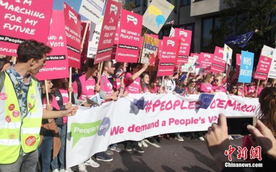 """资料图:10月20日,67万英国民众汇集在伦敦议会广场举行示威游行活动,呼吁对英国脱欧最终协议举行全民投票。图为示威游行队伍拉着横幅、举着标语牌,呼吁""""人民投票""""。社记者 张平 摄"""