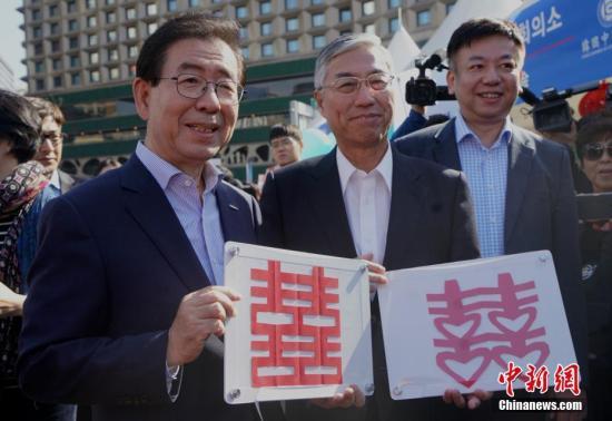 """10月21日,2018第六届""""首尔・中国日""""在首尔举行,一系列中国传统文化体验活动亮相。中国驻韩国大使邱国洪(右二)和韩国首尔市长朴元淳(左一)当天也亲临现场,并现场制作了剪纸窗花。<a target='_blank' href='http://www-chinanews-com.changxiangair.com/'>中新社</a>记者 曾鼐 摄"""