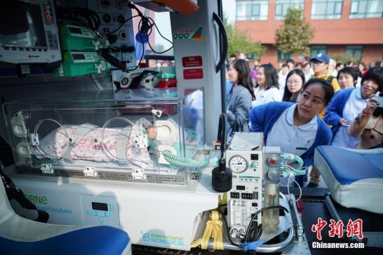 10月22日,999航空医疗救援队在北京儿童医院顺义妇儿医院举行演练,模拟河北省某地一名新生儿因病情危重,由直升机转运到北京儿童医院接受进一步救治的过程。而随着北京儿童医院与999急救中心在演练现场正式签署战略合作协议,中国首个固定翼、直升机、急救车立体化新生儿医疗转运体系也正式在北京地区搭建。该体系的运作将为北京及周边地区的新生儿紧急医疗转运开辟更加畅通的绿色通道。图为北京儿童医院顺义妇儿医院的医务人员观察999为该体系改装的新生儿专用航空医疗救援直升机内部结构。<a target='_blank' href='http://www-chinanews-com.apshaiwang.net/'>中新社</a>记者 崔楠 摄