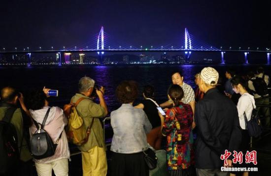 10月22日晚,游客在珠海乘坐游船近距离观赏即将通车的港珠澳大桥。港珠澳大桥即将于24日上午通车。 /p中新社记者 张炜 摄