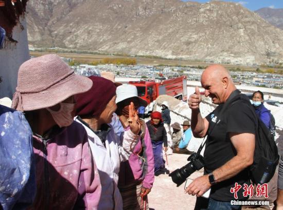 10月23日,来自美国加利福尼亚州的游客Tim游览布达拉宫时,遇到排队上山粉刷的信众,竖起大拇指为他们点赞。<a target='_blank' href='http://www-chinanews-com.linszone.com/'>中新社</a>记者 赵延 摄