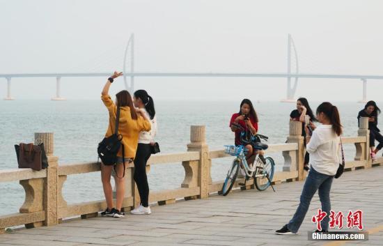 资料图:游客在广东珠海情侣南路海滨拍照留影,身后是港珠澳大桥。<a target='_blank'  data-cke-saved-href='http://www.chinanews.com/' href='http://www.chinanews.com/'>中新社</a>记者 张炜 摄