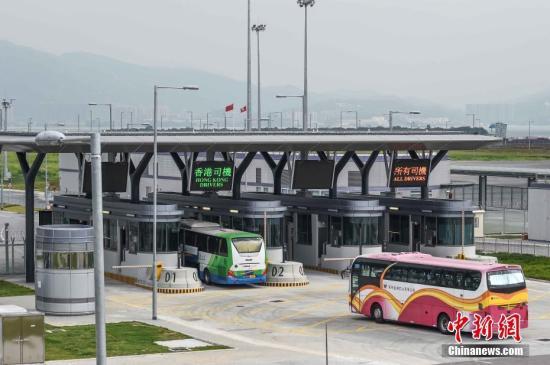 资料图:香港旅游巴驶经旅检大楼旁的闸口,准备登桥。<a target='_blank' href='http://www.chinanews.com/'>中新社</a>记者 麦尚�F 摄