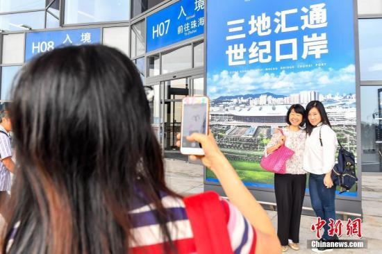 旅客在港珠澳大桥珠海公路口岸旅检楼拍照留念。<a target='_blank' href='http://www-chinanews-com.zgtyg.net/'>中新社</a>记者 陈骥�F 摄