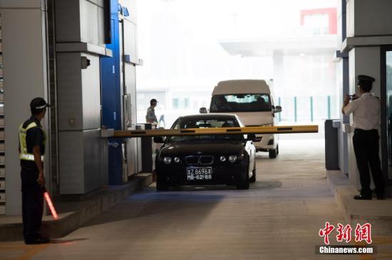 随着澳门口岸离境车道闸口开杆放行,首辆私家车驶过关口,港珠澳大桥正式通车运营。<a target='_blank' href='http://www-chinanews-com.ruoshuijt.com/'>中新社</a>发 钟欣 摄