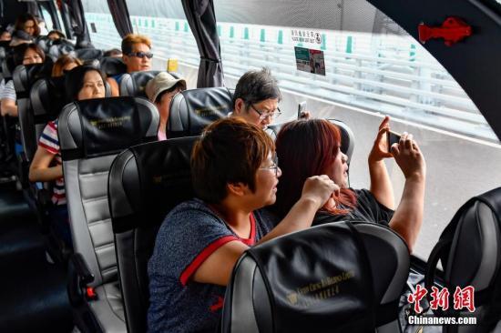 资料图:旅客乘坐大巴在港珠澳大桥上拍照留念。<a target='_blank' href='http://www.chinanews.com/'>中新社</a>记者 陈骥�F 摄