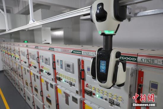 """10月26日,在距離首屆中國國際進口博覽會場館不遠的一座變電站里,智能巡檢機器人正帶著攝像頭""""一步一停"""",監控著一排排配電柜。據介紹,這里是國家電網為首屆進口博覽會""""保電""""的一座智能變電站。目前,首批15套電力巡檢機器人已在進博會核心區域投用,確保用電萬無一失。<a target='_blank' href='http://www.ongyu.icu/'>中新社</a>記者 張亨偉 攝"""