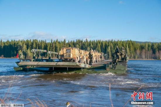 """北大西洋公约组织(北约)10月25日开始在挪威及其周边地区举行为期两周的""""三叉戟接点2018""""联合军事演习。这是北约自冷战结束以来规模最大的一次联合军演。图为英国第4步兵旅士兵携带器材穿过河流。"""