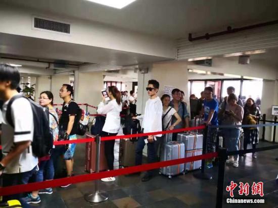 """受超级台风""""玉兔""""损毁严重一度关闭的美国塞班国际机场于当地时间10月28日起恢复开放。当日中午12时45分,接运因灾滞留中国游客的首架四川航空3U8648航班飞机搭载着295名乘客顺利起飞离开塞班岛。 <a target='_blank' href='http://www-chinanews-com.qfnmb.com/'>中新社</a>发 钟欣 摄"""