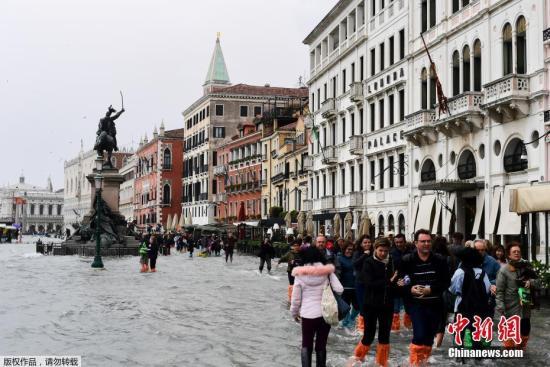 资料图:威尼斯城区水位急速上涨,威尼斯周边很多路段被水淹没。29日下午15时许,威尼斯地区降雨量达到了156毫米,70%的城区出现积水。威尼斯圣马可广场等旅游景区和轮渡禁止向游人开放。图为民众在威尼斯街头涉水前行。