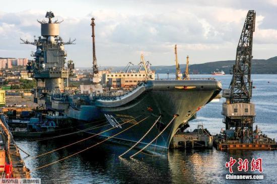 """当地时间10月30日,俄罗斯摩尔曼斯克,一艘世界上最大的浮动船坞(PD-50)在维修俄罗斯海军库兹涅佐夫号航母时突然沉没。这起事故发生在俄西北部港口城市摩尔曼斯克外的一个修船厂中,据报有四名员工落入水中。图为俄罗斯海军""""库兹涅佐夫""""号航空母舰。(资料图片)"""
