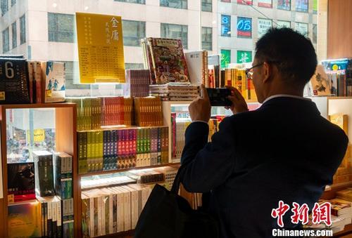 10月31日,在香港灣仔三聯書店,一位顧客正在金庸作品專櫃前拍照留念。10月30日,武俠小說泰鬥查良鏞(筆名金庸)在香港逝世,享年94歲。中新社記者 張煒 攝