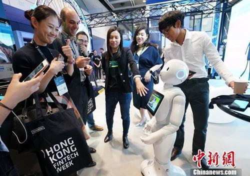 10月31日,2018香港金融科技周正式开幕。今年是香港金融管理局与香港投资推广署第三年合办香港金融科技周,金融科技周吸引了超过8000名高级管理人员参加,超过100家金融和科技企业参展,同时将会有200多位世界顶级金融科技的专家发表演讲。图为香港渣打银行推出的服务机器人与参观者互动,得到大家的点赞。<a target='_blank' href='http://www.chinanews.com/'>中新社</a>记者 张炜 摄