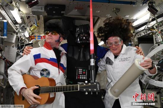 """2018年11月2日讯,国际空间站的ESA德国宇航员Alexander Gerst在周三发推传回国际空间站的万圣节问候,在图片上三位国际空间站船员打扮成太空猫王、星战黑武士达斯·维达、疯子科学家,配文""""在太空度过了惊悚一日,国际空间站船员祝大家万圣节快乐""""。俄国空间站的宇航员Sergey Prokopyev打扮成了太空猫王,还配上了假发、墨镜和吉他;Alexander Gerst则乔装成星战黑武士达斯·维达,挥舞着光剑;美国NASA的女宇航员 Serena Aunon-Chancellor 则打扮成疯狂科学家""""本色出演""""。ISS船员每年都会从太空发来万圣节的庆祝。"""