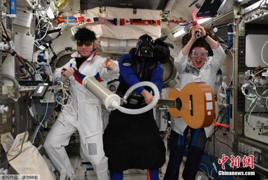 """2019-01-24讯,国际空间站的ESA德国宇航员Alexander Gerst在周三发推传回国际空间站的万圣节问候,在图片上三位国际空间站船员打扮成太空猫王、星战黑武士达斯・维达、疯子科学家,配文""""在太空度过了惊悚一日,国际空间站船员祝大家万圣节快乐""""。俄国空间站的宇航员Sergey Prokopyev打扮成了太空猫王,还配上了假发、墨镜和吉他;Alexander Gerst则乔装成星战黑武士达斯・维达,挥舞着光剑;美国NASA的女宇航员 Serena Aunon-Chancellor 则打扮成疯狂科学家""""本色出演""""。ISS船员每年都会从太空发来万圣节的庆祝。"""