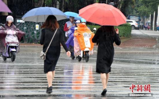 资料图:民众在雨中出行。张斌 摄