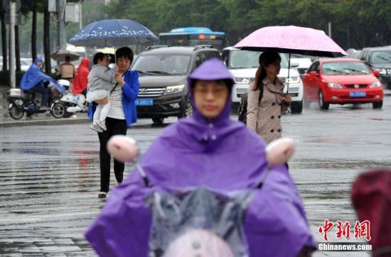 """11月2日,福州市民在雨中出行。今年第26号台风""""玉兔""""继续向中国东南部沿海靠近,并给福建各地带来明显的大风、降温及降雨影响。当日,福建省气象台发布台风黄色预警信号称,当天5时""""玉兔""""台风中心距离福建东山约355公里。张斌 摄"""