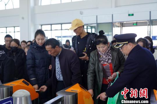 11月2日,青海西宁火车站乘客刷身份证进站乘车。图为西宁站工作人员指导旅客通过身份证识别区读取电子客票检票乘车。姚雪皎 摄