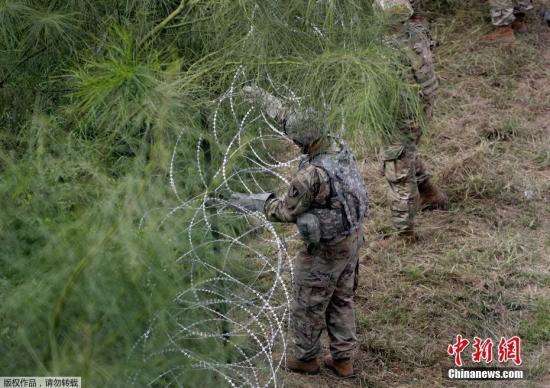 当地时间11月2日,美国得州Hidalgo,中美洲侨民大军压境美国,美国士兵在美墨边境装配铁丝网厉防侨民入境。