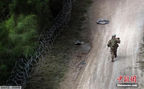 资料图:当地时间11月2日,美国得州Hidalgo,中美洲移民大军压境美国,美国士兵在美墨边境安装铁丝网严防移民入境。