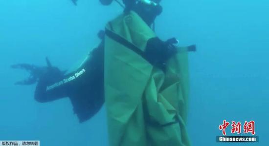 2018年11月4日讯,印尼失事客机残骸打捞工作持续,潜水员在印尼狮航客机失事海域收集客机残骸。(视频截图)