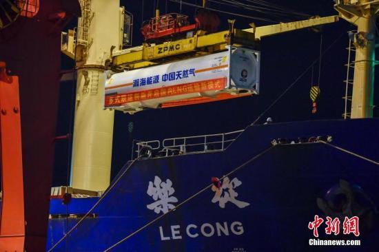 图为11月2日晚,首个LNG罐箱运抵海南洋浦港,开始吊装上船。 骆云飞 摄