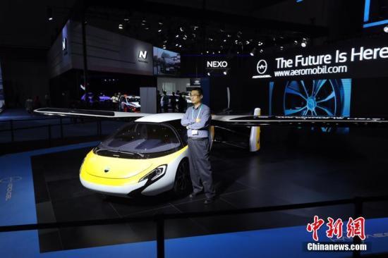 """进博会最科幻展品之一""""会飞的汽车""""吸引参会者合影。张亨伟 摄"""