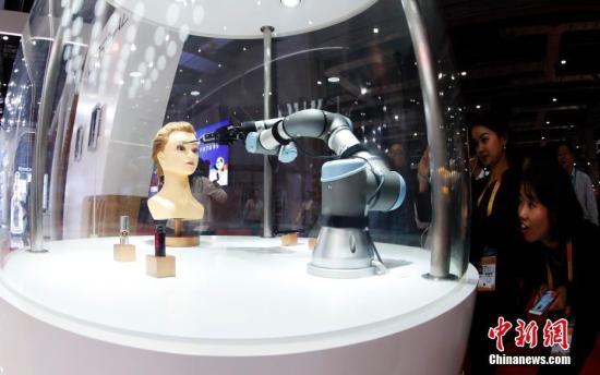 11月5日,在首届进博会的欧莱雅展台上,一款美妆机器人吸引了许多女性参观者的目光。该机器人会画眉毛刷腮红,5分钟能完成一个妆容。当日,首届中国国际进口博览会在上海开幕,来自130多个国家和地区的3000多家企业前来参展。汤彦俊 摄