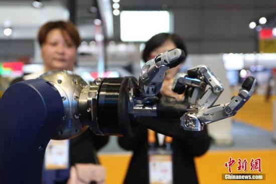 """11月5日,首届中国国际进口博览会隆重开幕。本届展会最""""心灵手巧""""的展品之一SVH仿人五指机械手亮相。这款机械手尺寸、外形和灵活性与人手相似程度极高,曾在德国汉诺威工业博览会上与德国总理默克尔""""握手""""。凭借带有9个驱动器的运动指骨和富有弹性的表面,它不仅能拿钥匙开锁,就连捡起一根针这种精细活儿也能胜任。张亨伟 摄"""