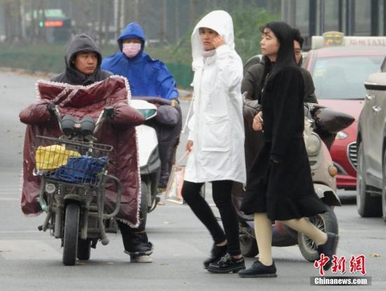 """11月5日,河南郑州,气温下降,民众""""全副武装""""御寒。据中国天气网消息,当日冷空气继续南下,郑州降温明显,累计降幅可达13℃。中新社记者 王中举 摄"""