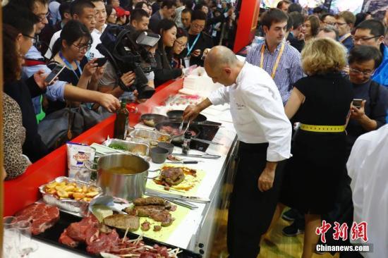 11月6日,进博会食品及农产品展区内厨师为观众烹饪美食。11月5日,首届中国国际进口博览会在上海开幕,来自130多个国家和地区的3000多家企业前来参展。<a target='_blank' href='http://www-chinanews-com.hrhgj.com/'>中新社</a>记者 富田 摄