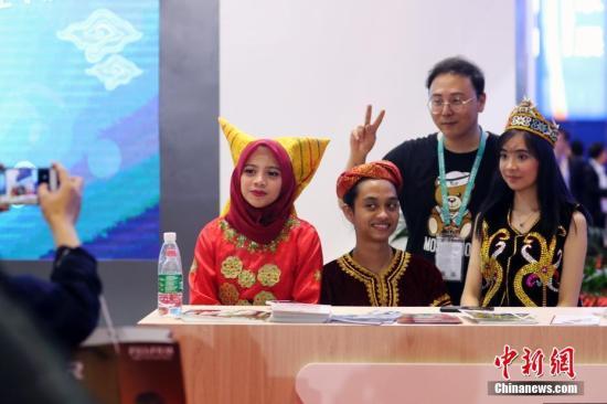 资料图:在首届中国国际进口博览会上,印度尼西亚展台盛装的工作人员吸引不少参观者合影。中新社记者 盛佳鹏 摄