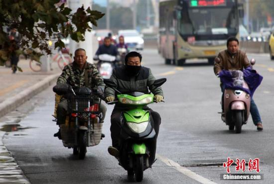 11月6日,河南多地遭遇阴雨天气,气温骤降。郑州的市民纷纷穿上厚衣服抵御寒冷。<a target='_blank' >中新社</a>记者 王中举 摄