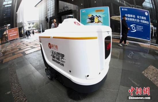 """11月7日,在浙江乌镇举行的第五届世界互联网大会""""互联网之光""""博览会会场内,无人驾驶扫地机器人保障路面干净整洁。中新社记者 杜洋 摄"""