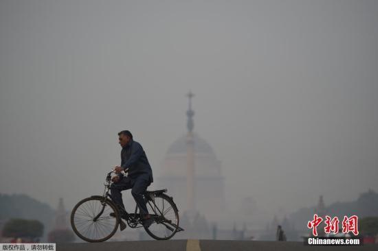 資料圖:當地時間11月8日,印度新德里被霧霾籠罩。新德里的空氣污染水平在冬季飆升,排燈節燃放煙花加劇污染,當地民眾紛紛戴上口罩防霧霾。