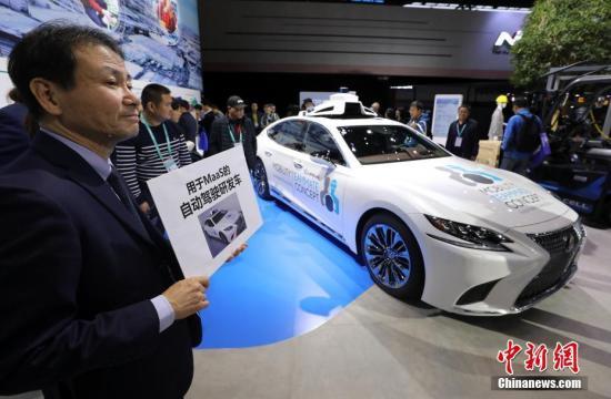 11月8日,上海进博会汽车展馆,日本汽车技术研发人员在现场手持展示牌为参观者导引解说。中新社记者 毛建军 摄