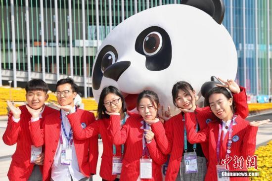 """11月10日,首届中国国际进口博览会完善终结。进博会自愿者""""幼叶子""""(昵称)在国家会展中心(上海)南广场相符影留念,留住喜悦时光。中新社记者 张亨伟 摄"""