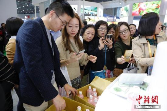 11月10日,首届中国国际进口博览会食品及农产品展区,参观者扫码支付购买商品。<a target='_blank' href='http://www-chinanews-com.huakui.net/'>中新社</a>记者 殷立勤 摄