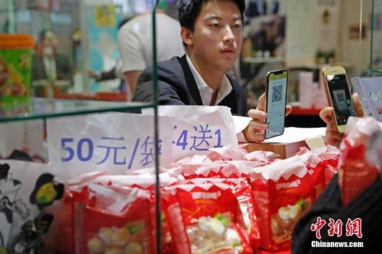 11月10日,首届中国国际进口博览会食品及农产品展区,参观者扫码支付购买商品。记者 殷立勤 摄